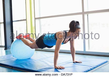 Woman exercising with fitness ball in fitness center - Stock Photo