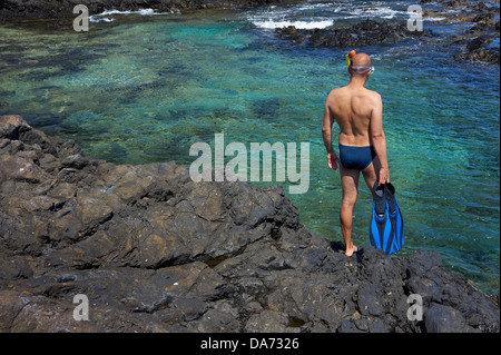Young man with snorkeling equipment on the rock coast. Canary Islands, Lanzarote. - Stock Photo