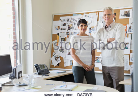 Portrait of business colleagues standing together in office - Stock Photo