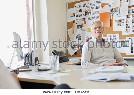 Businessman sitting at desk in office - Stock Photo