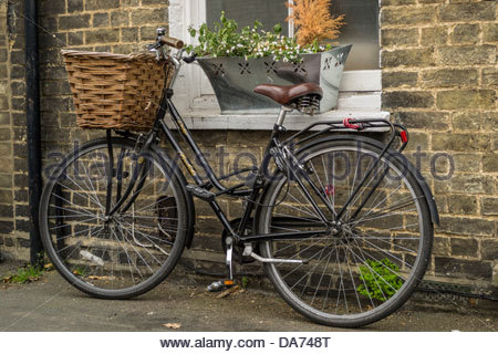 Traditional style bicycle with a wicker basket on the front locked up outside a terraced house in Cambridge - Stock Photo