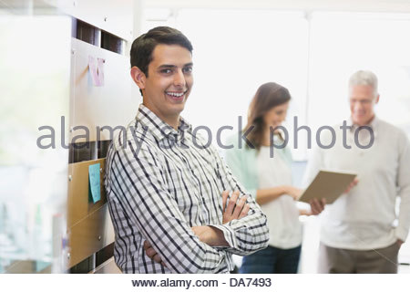 Portrait of businessman standing arms crossed in office - Stock Photo