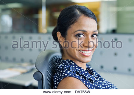 Portrait of smiling businesswoman sitting in office - Stock Photo