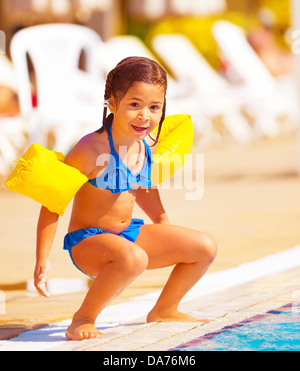 Cute little girl preparing to jump into water, having fun in the pool, luxury beach resort, summer time in daycare - Stock Photo