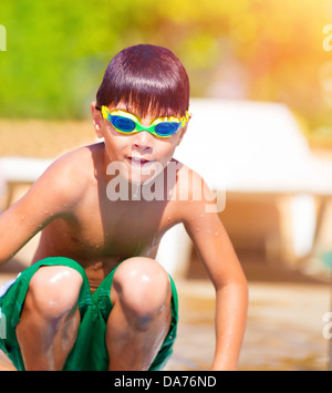 Sporty boy jumping into the pool, wearing swimmer goggles, active childhood, water sport, summer vacation - Stock Photo