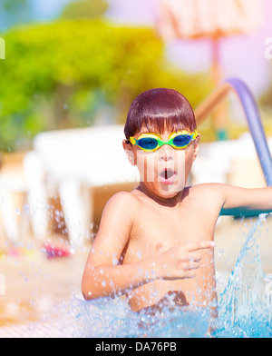 Closeup on pretty boy having fun in the pool, adorable child wearing swimming goggles, summer holidays on luxury - Stock Photo