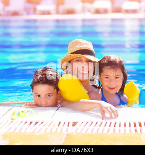 Closeup portrait of young arabic mother with two adorable children swimming in the pool, happy family on beach resort - Stock Photo