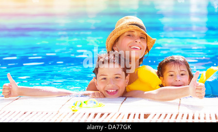 Happy family have fun in the pool, relaxation in aquapark, mother with two cute kids swimming in cool water - Stock Photo