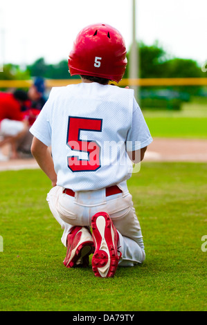 Baseball boy kneeling on the ground while an injured player is on the field. - Stock Photo