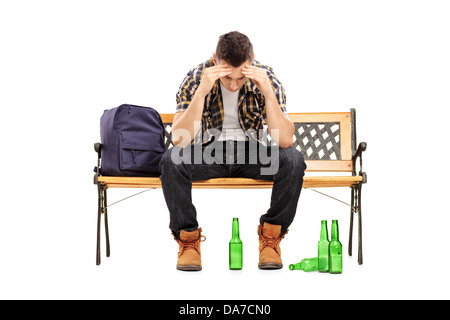 Young man with hangover sitting on a bench, empty beer bottles on the ground - Stock Photo