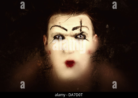 Portrait of a terrible mime with blue eyes through the dirty glass - Stock Photo