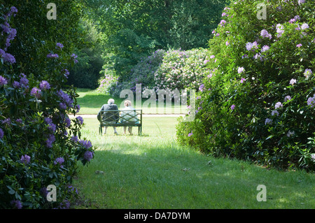 Elders couple sitting on bench in garden retreat. Blickling Hall gardens, Norfolk, UK. - Stock Photo