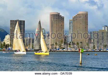 Sailboat departing Ala Wai Boat Harbor in Honolulu, Hawaii. - Stock Photo