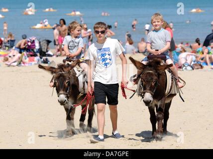 Donkey rides on Weymouth Beach, children enjoy a donkey ride, Dorset, Britain, UK - Stock Photo