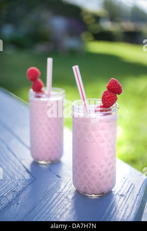 two raspberry smoothies outside on a sunny day - Stock Photo
