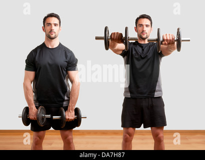 Personal Trainer doing front dumbell raises for training his deltoids, in a gym - Stock Photo