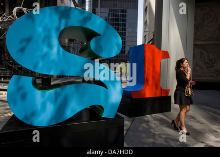 A woman smokes a cigarette by a large red number One and Two, part of an art installation entitled 'One Through - Stock Photo