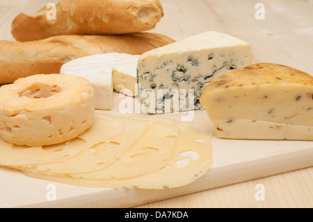 Various Types of Cheese on Wooden Chopping Board - Stock Photo