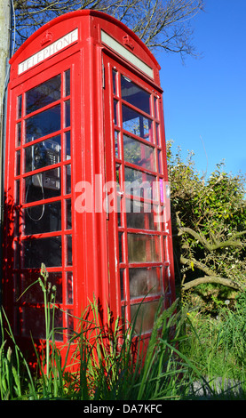 Traditional Red British Telephone Box or booth in a country setting - Stock Photo