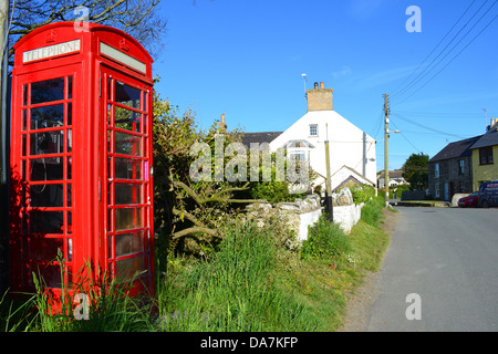 Traditional red British telephone box on a village lane. - Stock Photo