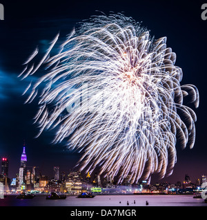 Macy's 4th of July fireworks on the Hudson river with the Manhattan skyline and the Empire State Building in the - Stock Photo