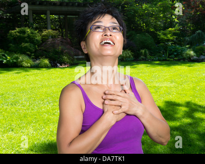 An Asian woman has a moment of enlightenment in her garden - Stock Photo