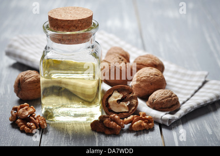 Walnut oil with nuts on a wooden background - Stock Photo