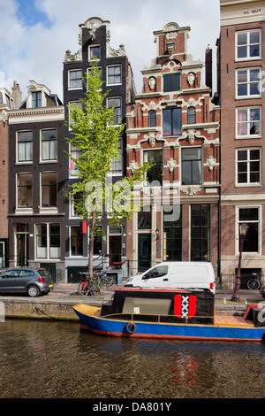 Traditional Dutch style houses along the canal in Amsterdam, Netherlands. - Stock Photo