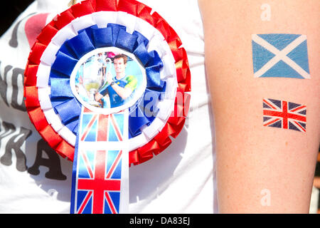 Wimbledon London UK. 7th July 2013. A tennis  fan wears a Rosette Ribbon to support Andy Murray  as he prepares - Stock Photo