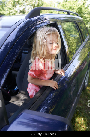 Little blond girl child playing inside a car - Stock Photo