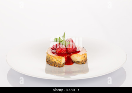 Cheesecake with strawberry, red coulis and mint on white plate. - Stock Photo