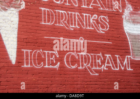 Advertising sign painted on the outside of a vintage diner advertising fountain drinks and ice cream. Sign is painted - Stock Photo