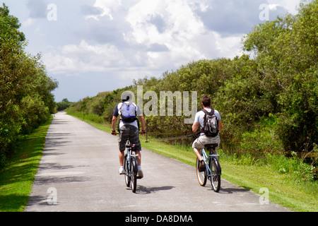 Miami Florida Tamiami Trail Everglades National Park Shark Valley bike trail rental bicycles teen boy biking - Stock Photo