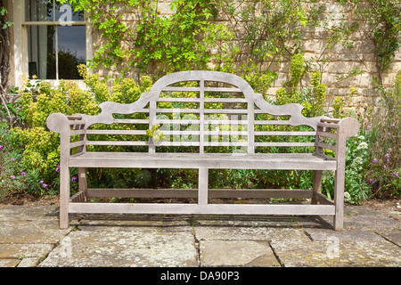 Old garden bench situated in a landscaped garden. - Stock Photo
