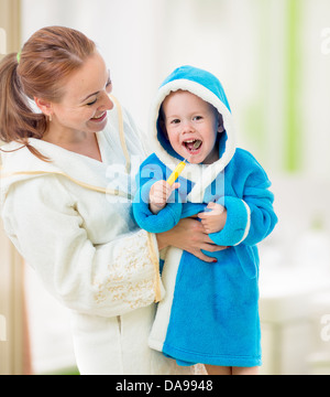 mother and child brushing teeth together in bathroom. Dental hygiene. - Stock Photo