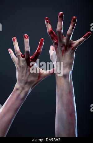 Bloody zombie hands, studio shot over gray background  - Stock Photo