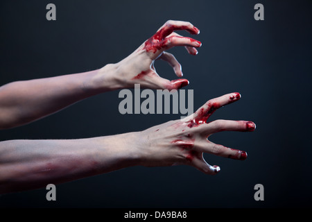 Zombie stretching his bloody hands, studio shot over gray background  - Stock Photo