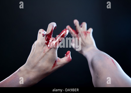 Pale bloody zombie hands, studio shot over gray background  - Stock Photo