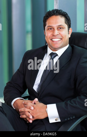 cheerful Indian business man sitting in modern office - Stock Photo