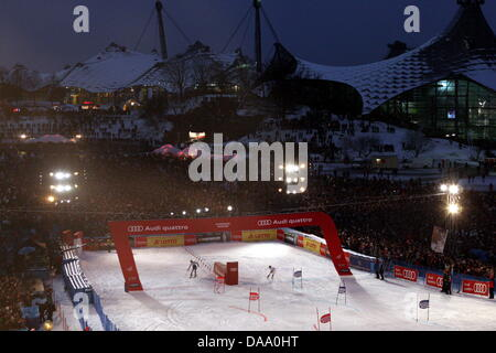 Two downhill skiers arrive in a race at the finishing line during the FIS Alpine Ski World Cup event in Munich, - Stock Photo