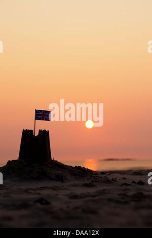 Sandcastle with flag silhouette at sunrise on a beach. Northumberland, England - Stock Photo