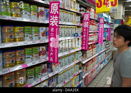 A man looks at imported infant formula baby milk powder in a supermarket in Beijing, China. 09-Jul-2013 - Stock Photo