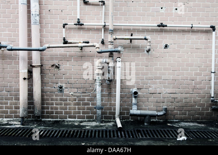 It's a photo of some pipes along the wall. It's the plumbing of the house or building. Wee see its wall. - Stock Photo