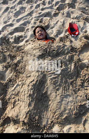It's a photo of a kid cover in sand or silt or bury in the sand beach for fun - Stock Photo