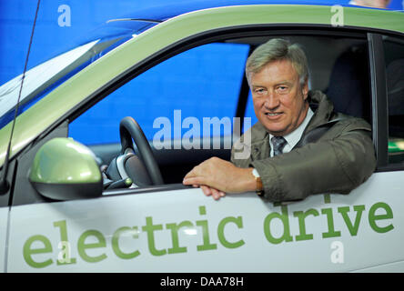 Former mayor of Hamburg Ole von Beust pose for a  picture in a Smart car in front of a charging station for electric - Stock Photo