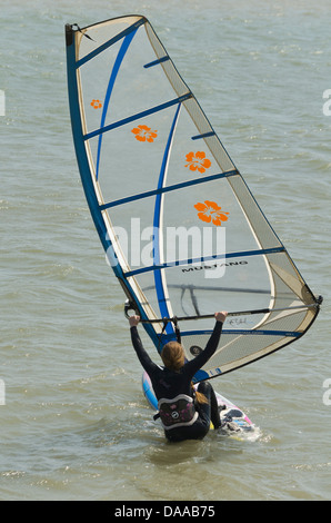 woman getting onto her sailboard - Stock Photo