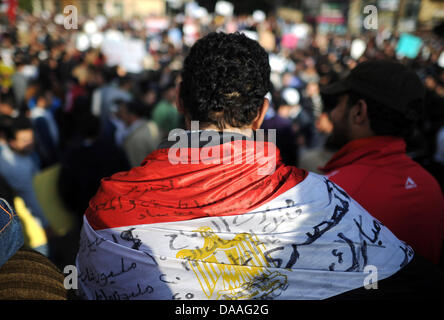 A demonstrator has wound the Egyptian flag around his shoulders at the Tharir Square in Cairo, Egypt, 31 January - Stock Photo