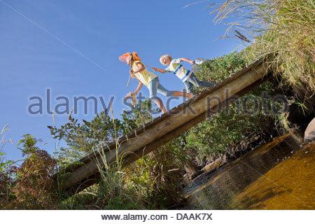 Happy boy and girl with fishing nets walking on footbridge over stream - Stock Photo