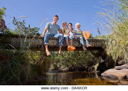 Portrait of smiling family sitting on footbridge over stream - Stock Photo