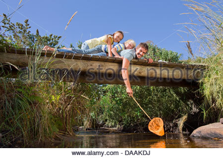 Portrait of smiling father, daughter and son with fishing net laying on footbridge over stream - Stock Photo